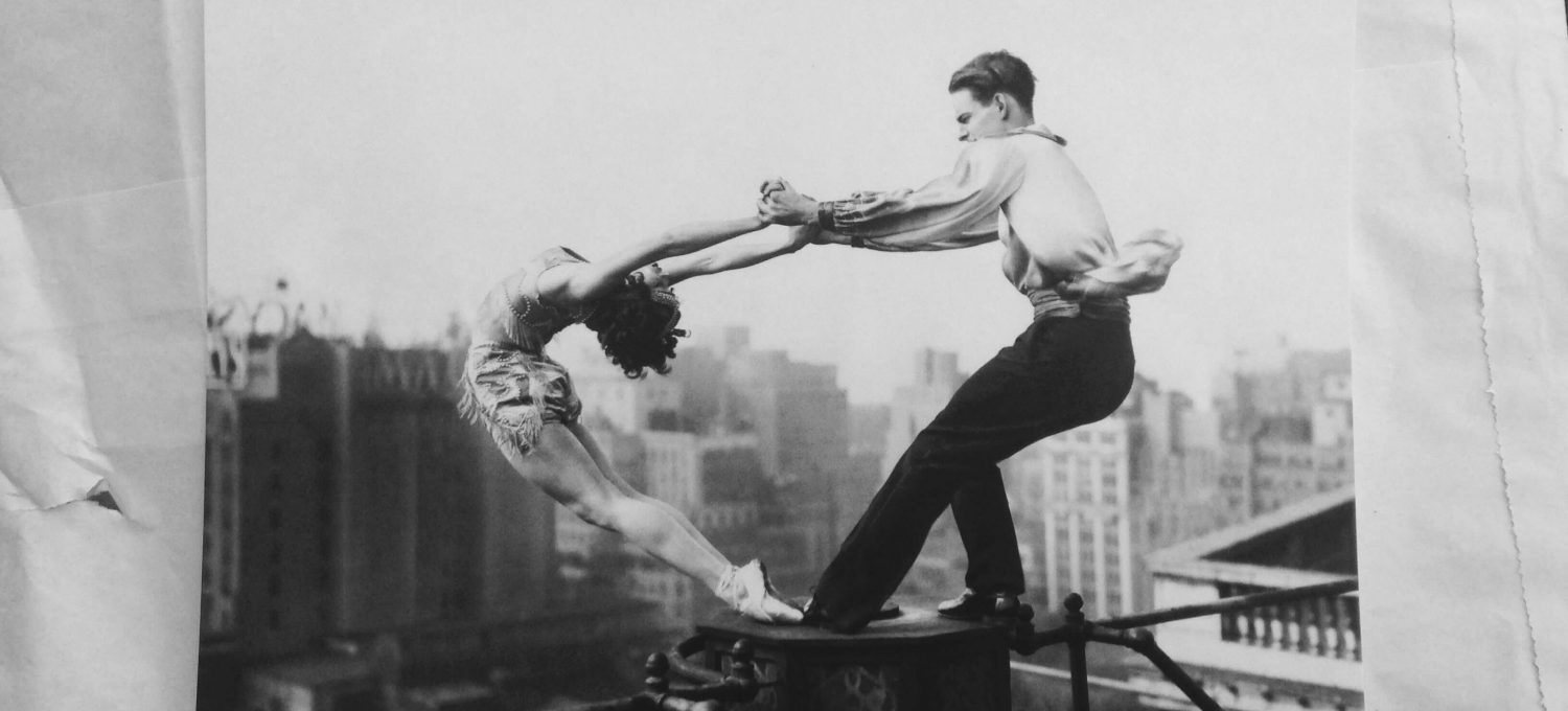 A black and white photograph of two dancers in a dangerous position dancing on a rooftop