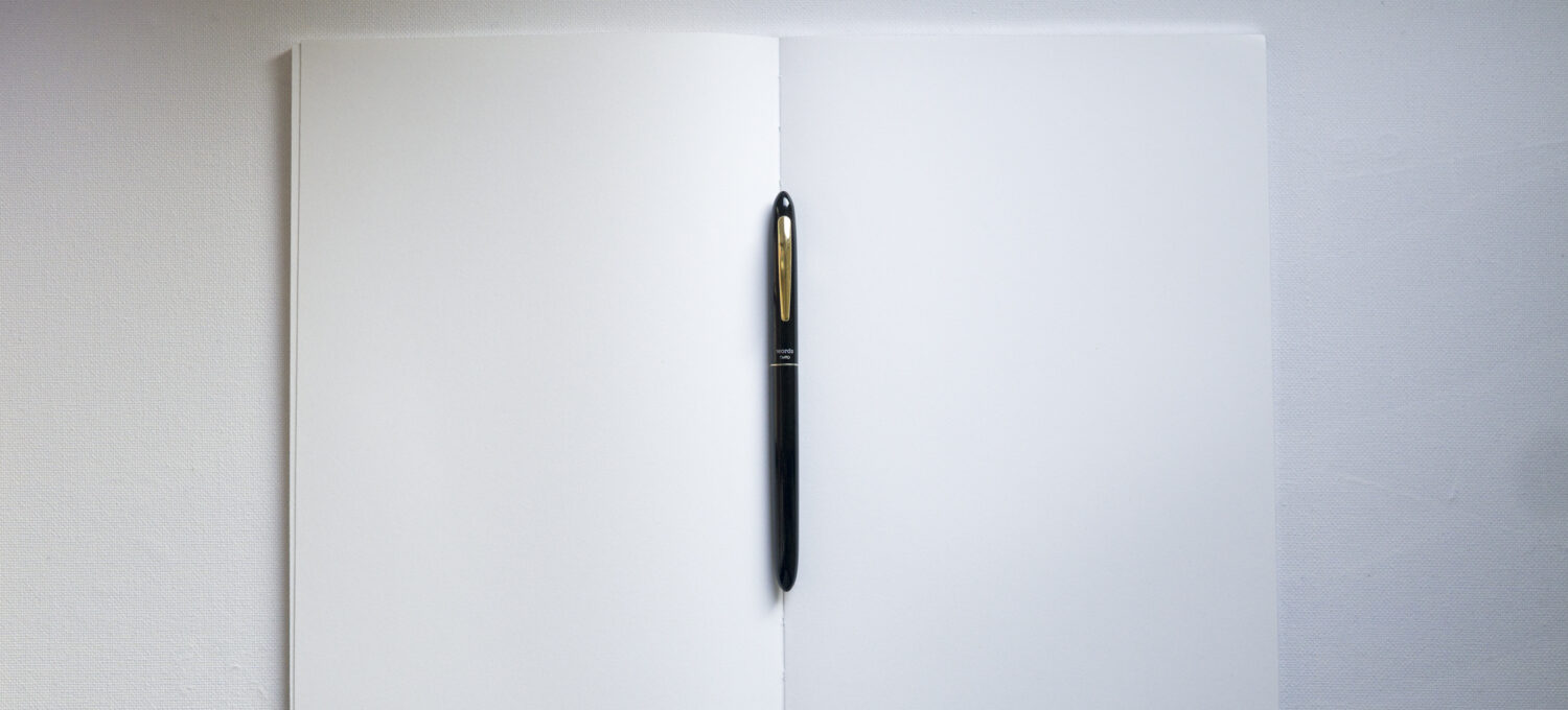 From above shot of an opened notebook and a pen laying right in the middle of it. The pages are blank, the pen is black.